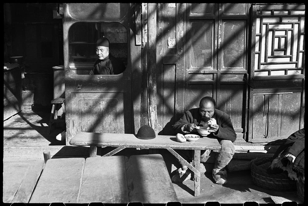 亨利.卡蒂耶-布列松,《坐在食肆窗內的跑堂或店主,苦力在簷下用餐,北平,1948年12月》