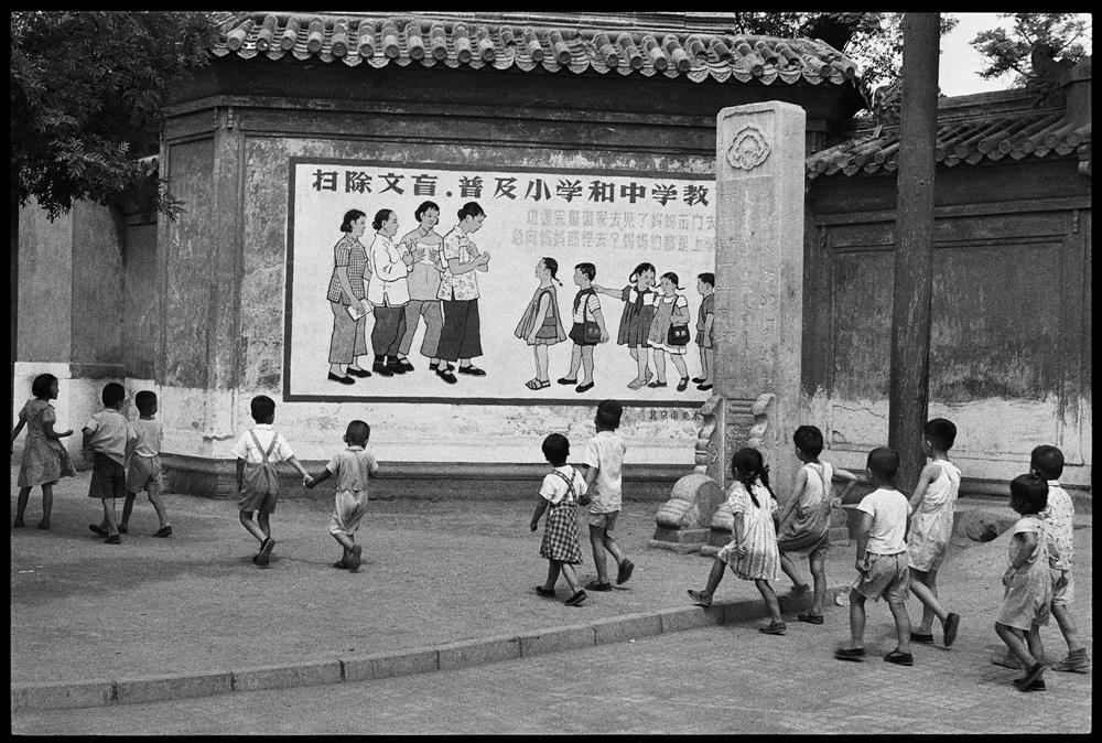 亨利.卡蒂耶-布列松,《孩童正從一幅寫著「…媽媽們都是上學去…」宣傳標語的看板前經過,北京,1958年7月》