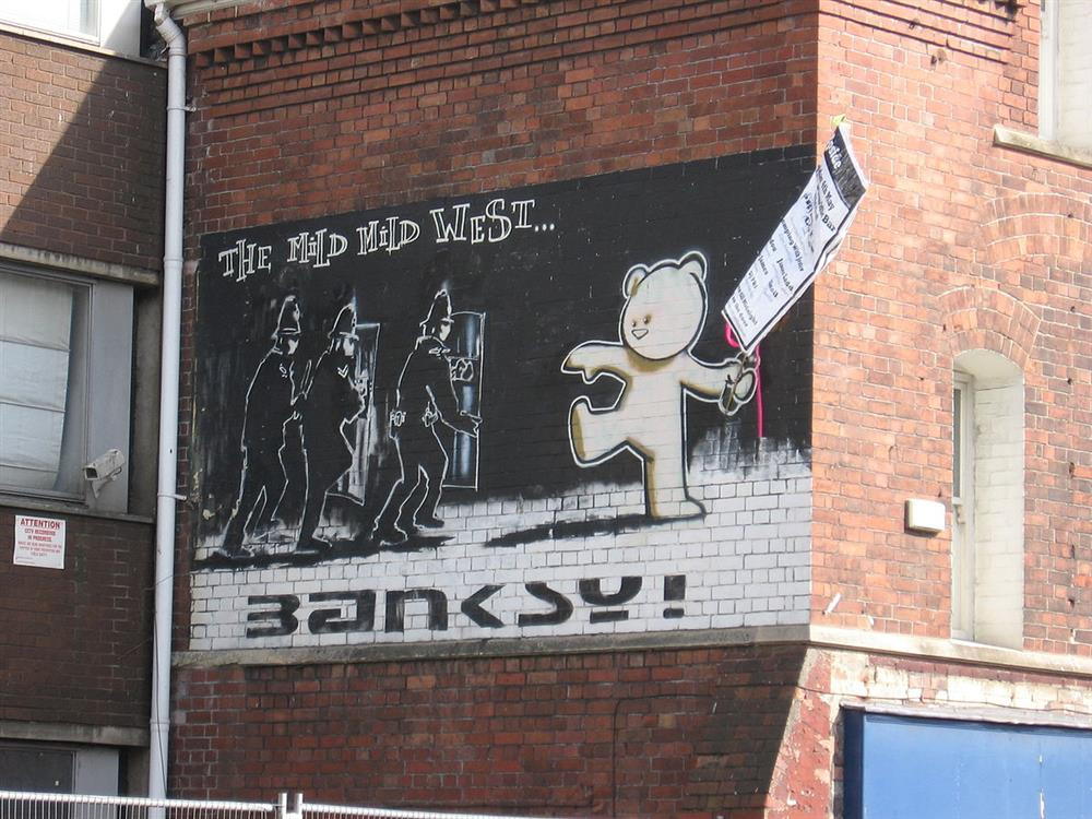 1200px-Banksy_MIld_Mild_West_and_poster