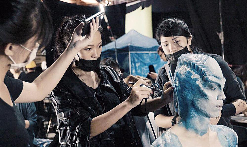 程薇穎正在替演員上妝,製造電影《吃吃的愛》蜥蜴人的妝感。