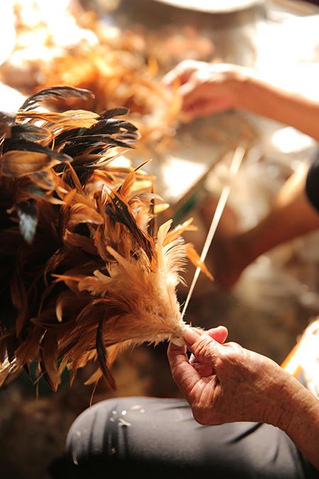 老師傅左手轉動木軸棒、右手熟練地挑撿 出合適羽毛,將雞羽一片一片黏上木棒, 同時轉動木軸,雞毛撢子逐漸在手中成形。