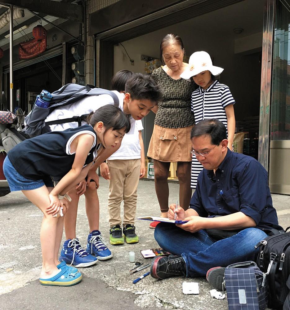 渡邉先生隨地坐下手繪建築時,也吸引不少民眾好奇地圍觀。